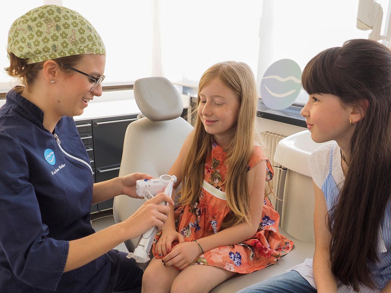 Un'igenista dentale dello studio insegna a due bambine come lavarsi i denti
